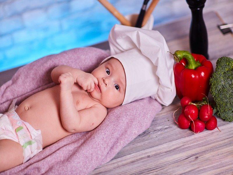 Bébé allongé sur une serviette avec une toque de cuisinier sur la tête. A côté de lui il y a un poivron rouge, un brocoli et des radiset